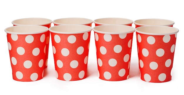 Group of cardboard disposable red dotted cups isolated