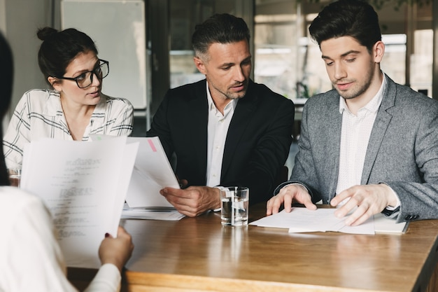 Group of caucasian people in formal suits sitting at table in office, and talking with young woman during job interview - business, career and recruitment concept