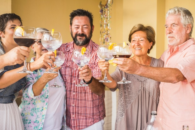 Group of caucasian people friends with different ages celebrate together cheering with cocktails all together having fun