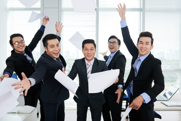 Group of cheerful asian businessmen in suits throwing documents up in air in office