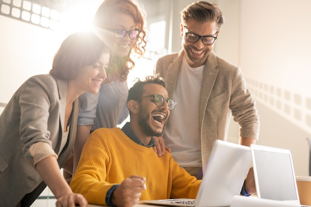 Group of cheerful excited young interracial colleagues laughing while reading internet news on laptop