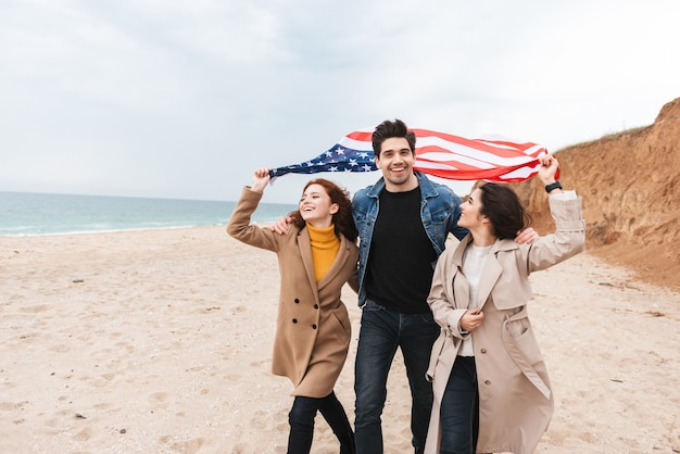 Group of cheerful friends running at the beach carrying american flag