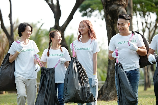 Group of cheerful friends volunteering in local park and picking up trash to clean the ground