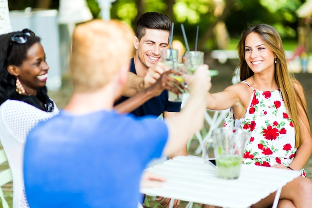 Group of cheerful happy people toasting while sitting at a table outdoors on a hot summer day