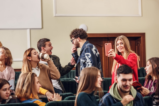 The group of cheerful happy students sitting in a lecture hall before lesson