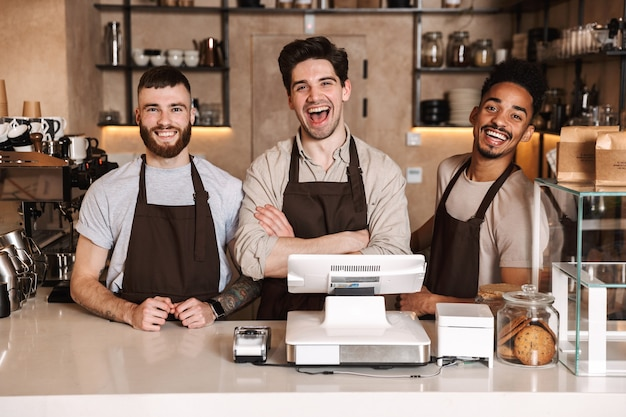 Group of cheerful men baristas wearing aprons working at the counter in cafe indoors, arms folded