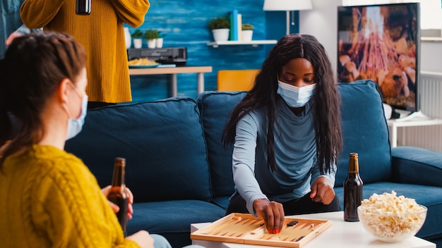Group of cheerful multiethnic friends playing board games backgammon board games keeping social distancing wearing face mask to prevent infection with covid19 during global pandemic drinking beer