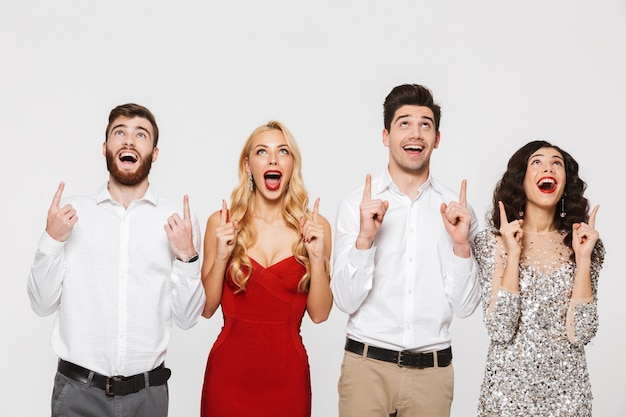 Group of cheerful smart dressed friends standing isolated over white, celebrating new year, pointing fingers up