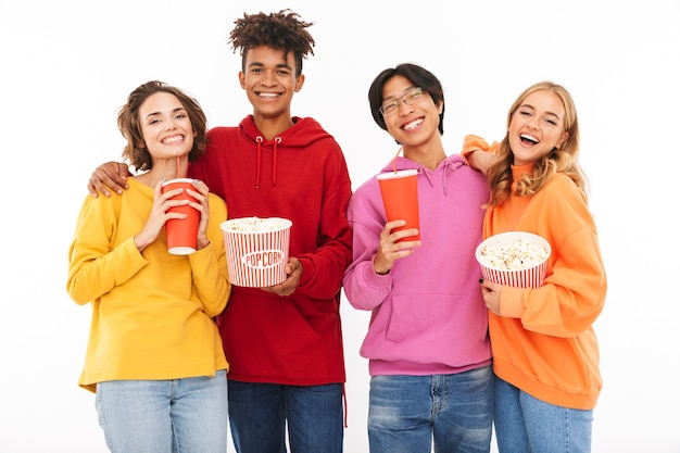 Group of cheerful teenagers isolated, watching a movie, eating popcorn