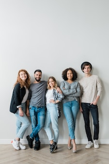 Group of cheerful young affectionate friends in jeans and pullovers standing by white wall