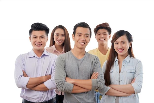 Gruppo di giovani allegri in posa casualmente vestita di donne e uomini