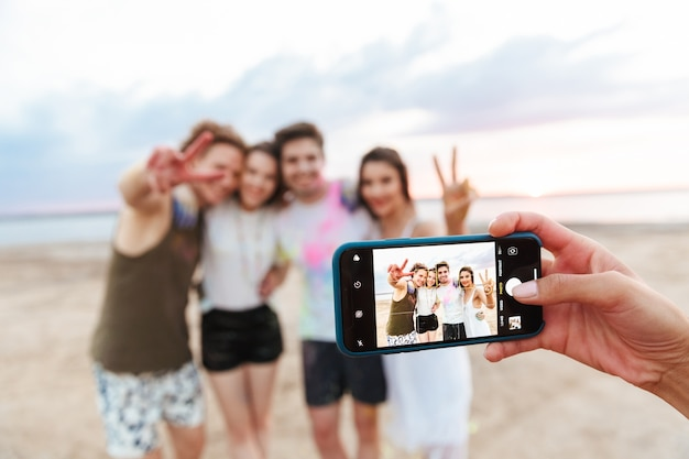 Group of a cheerful young friends having fun at the beach with colorful holi paint, getting photographed