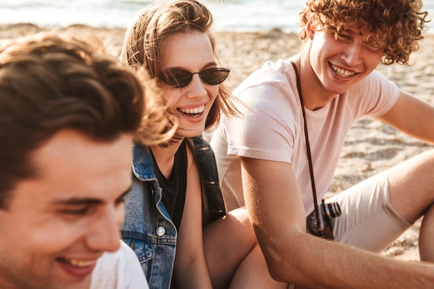 Group of cheerful young friends having fun time together at the beach