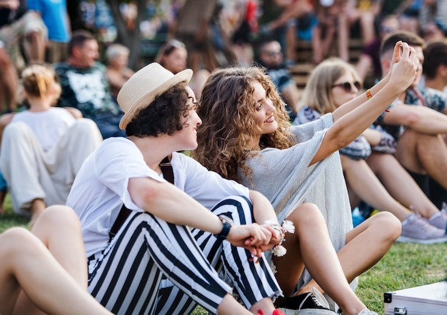 Group of cheerful young friends sitting on ground at summer festival, taking selfie.