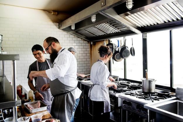 Gruppo di cuochi che lavorano in cucina