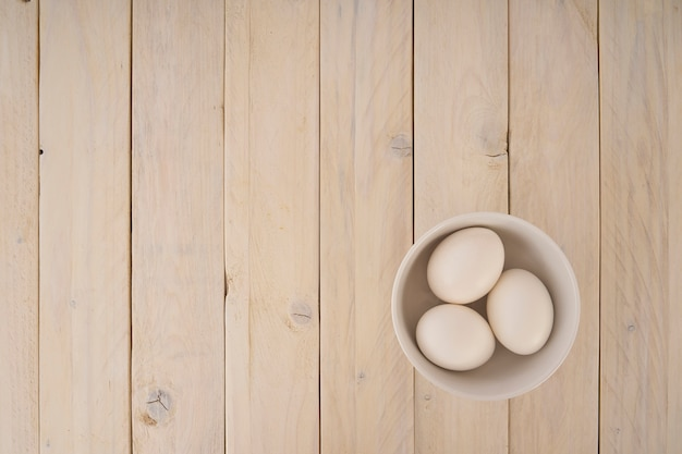 Group of chicken eggs in a bowl on wooden background