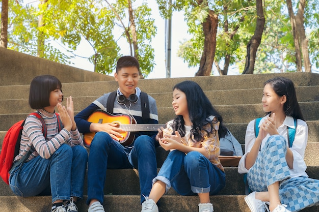 Group of child student playing guitar and singing songs together in summer park