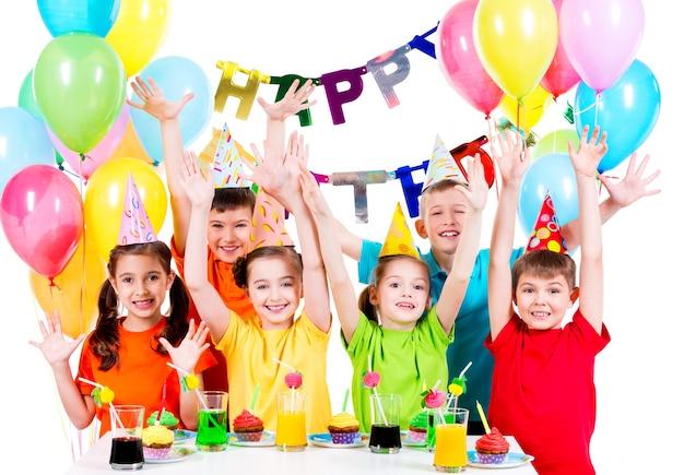 Gruppo di bambini in camicie colorate alla festa di compleanno con le mani alzate - isolato su un bianco