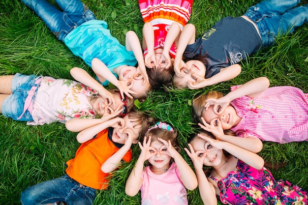 A group of children lying on the green grass in the park. the interaction of the children.