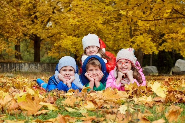 Group of children lying in a park on yellow leaves in autumn park on nature.