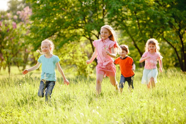 A group of children playing and running in the park on a green gozon.