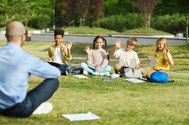 Group of children raising hands while sitting in row on green grass and answering teachers questions in outdoor class, copy space