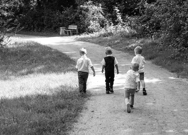 Group of children running along path towards in park