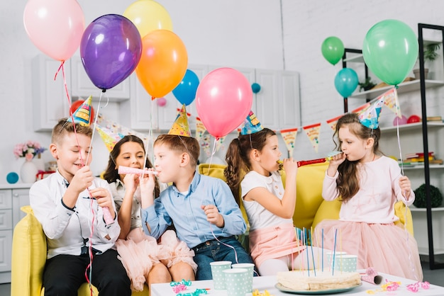 Group of children sitting on sofa holding colorful balloons and blowing party horn