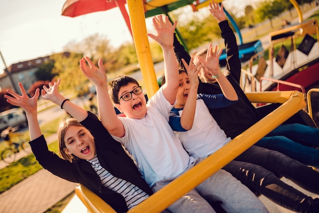 Group of children on a spinning ride in amusement park