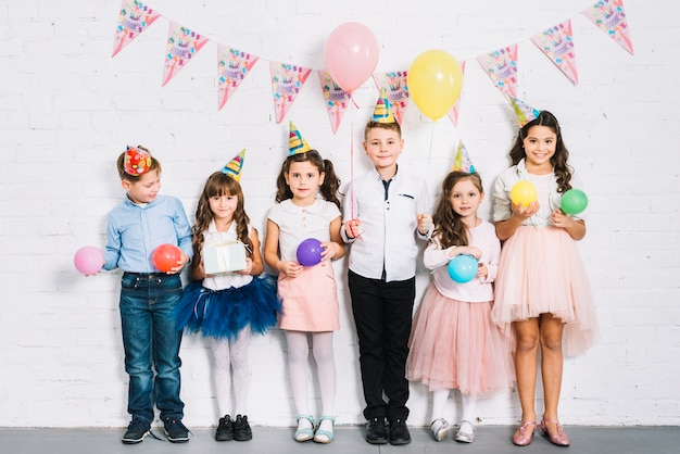 Group of children standing against wall holding balloons in hand at birthday party