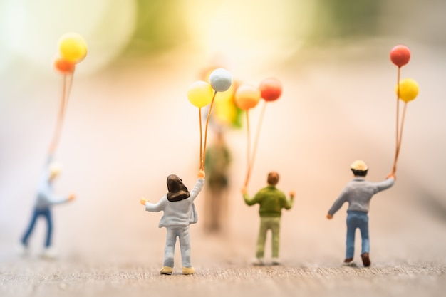 Group of children standing and walking abd running to a man balloon seller
