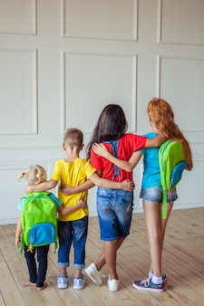 Group of children of students of different ages with backpacks in colorful clothes back view