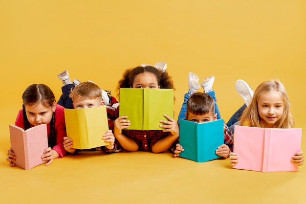 Group of childrens covering their faces with books