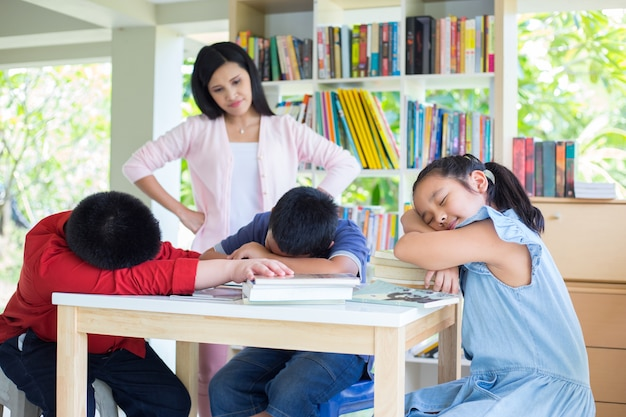 Group of childrens sleeping at the desk and a teacher woman standing behind