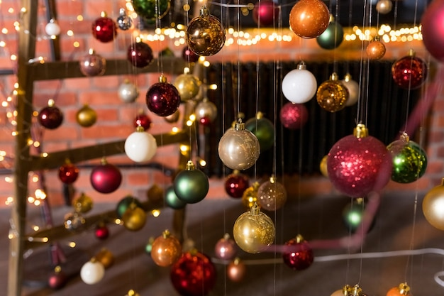 A group of christmas balls hanging on thin threads on blurred background happy new year theme greeting cardcolorful christmas small balls hang on ribbons