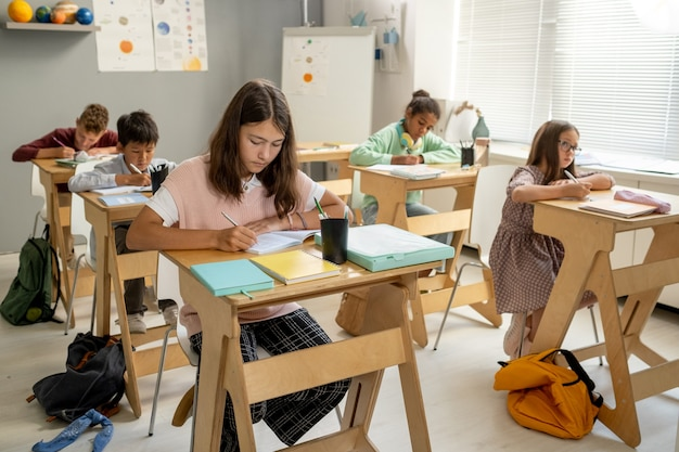 Group of clever intercultural schoolchildren working individually