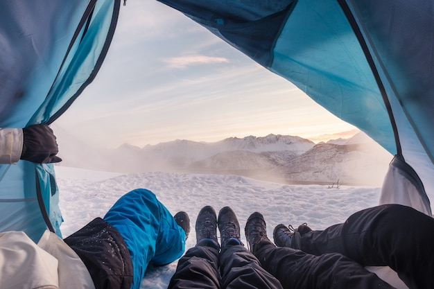 Group of climber are inside a tent with open for view of blizzard on mountain