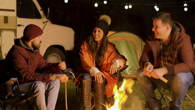 Group of close friend relaxing together around camp fire in a cold night of autumn. retro camper van. camping tent.