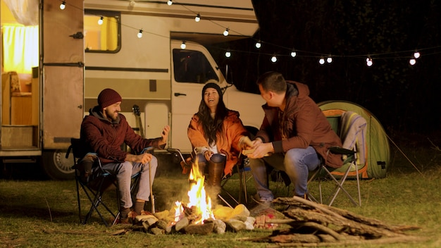 Group of close friends laughing together around camp fire. retro camper van. light bulbs in the background.