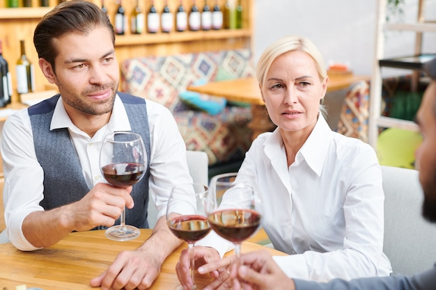 Group of colleagues in formalwear discussing quality and other characteristics of red wine in wineglasses during work