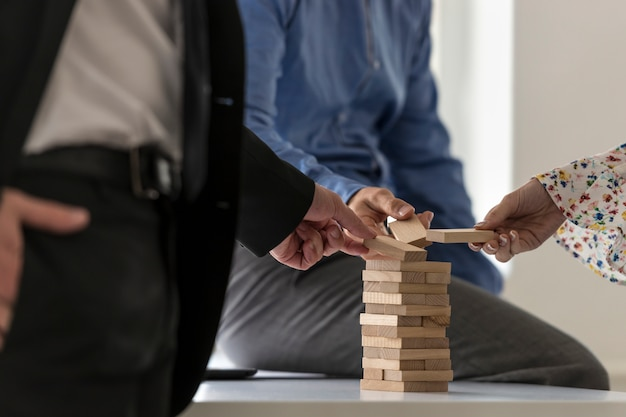 Group of colleagues in an office carefully building a tower of wood blocks