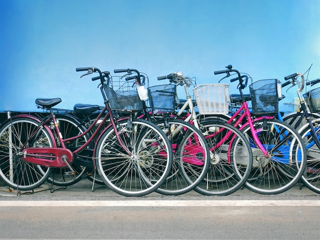 Group of colorful bicycles with front baskets parked by the road against blue wall