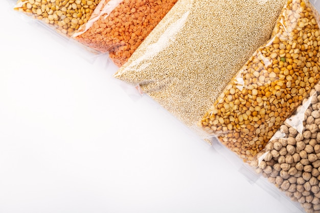 Group of colorful various cereals and legumes in plastic wrap on white wall with copyspace.