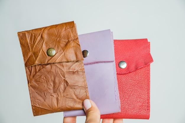 白い背景の上の革の皮のカラフルな財布をグループ化します。ファッショナブルでモダンなレザーポーチ
