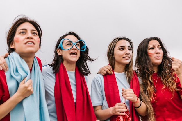 Group of concentrated female soccer fans supporting their team at stadium