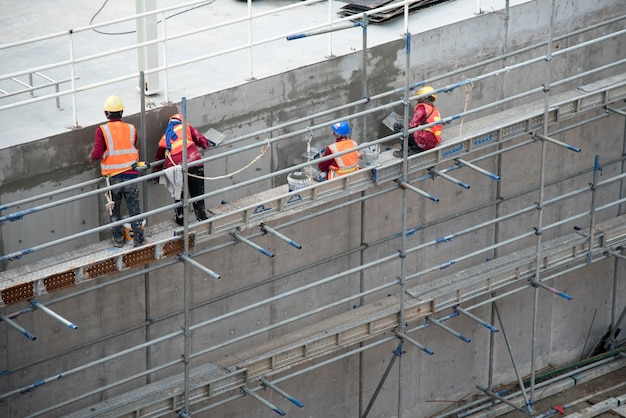 Group of construction worker plastering cement concrete water tank in construction area