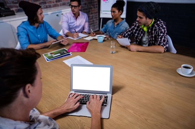 Group of coworkers during meeting and laptop
