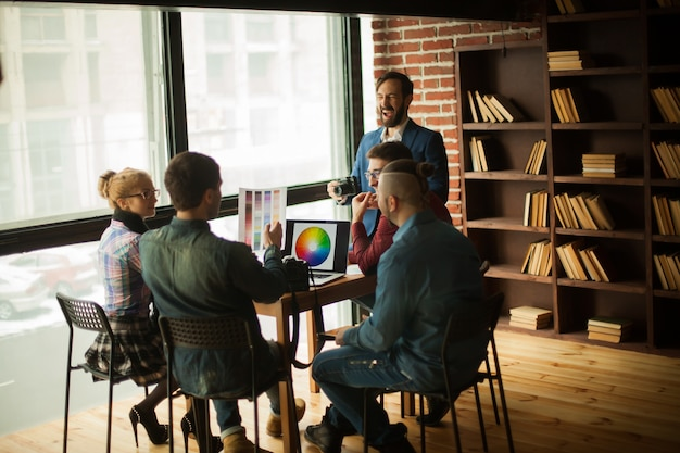 Group of creative designers discussing a new color palette in the workplace in a modern office
