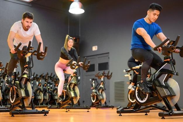 Групповая езда на современном фитнес-велосипеде во время группового спиннинга в тренажерном зале