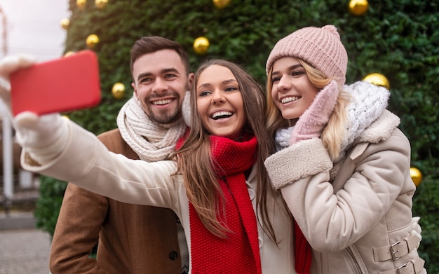 Group of delighted young friends in warm clothes standing against green christmas tree and taking selfie on smartphone while spending holidays together in city